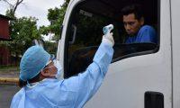 Una enfermera del área de salud de Izabal toma muestra de temperatura a un piloto procedente de El Salvador, en el puesto fronterizo entre Guatemala y Honduras. (Foto Prensa Libre: Dony Stewart)