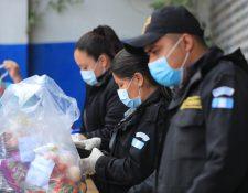 Custodios del Sistema Penitenciario revisan con guantes y mascarilla una bolsa con alimentos en el Centro Preventivo para Varones, en la zona 18.   (Foto Prensa Libre: Juan Diego González)