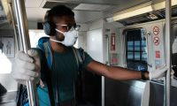 NEW YORK, NEW YORK - MARCH 07: A man wears a medical mask on the AirTrain as concern over the coronavirus grows enroute to John F. Kennedy Airport (JFK) on March 7, 2020 in New York City. The number of global coronavirus infections has now surpassed 100,000, causing disruptions throughout the globe. The airline and travel industries has been especially hard hit by the outbreak, with both business and leisure travelers cancelling plans.   Spencer Platt/Getty Images/AFP == FOR NEWSPAPERS, INTERNET, TELCOS & TELEVISION USE ONLY ==