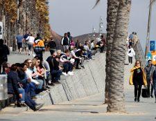 Varias personas toman el sol cerca de la playa de Barcelona a pesar las medidas que se han adoptado en otras ciudades por el covid-19. (Foto Prensa Libre. AFP)