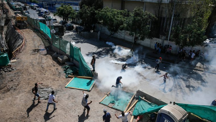 """Los familiares de los reclusos de la cárcel """"Santiago 1"""" chocan con las fuerzas de seguridad fuera de la prisión en Santiago de  Chile. (Foto Prensa Libre: AFP)"""