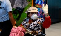 A passenger waves as she wears a face mask as a precaution against the spread of the new coronavirus, at La Aurora International Airport in Guatemala City, on March 12, 2020. (Photo by Johan ORDONEZ / AFP)