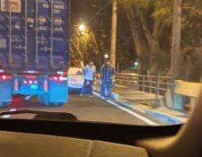 Dos jovenes con guantes y mascarillas esperan el paso de los camiones de carga a la orilla de la ruta. (Foto Prensa Libre: Héctor Yumas)