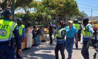 Oficiales de Tránsito de Villa Nueva tratan de persuadir a personas que descansan en el parque central de la localidad a que regresen a sus casas. (Foto: Cortesía)
