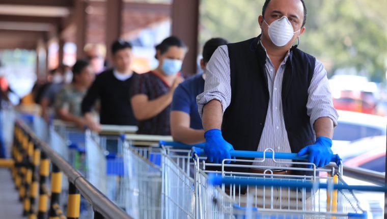 Clientes esperan su turno para ingresar a uno de los supermercados, en los cuales se toman las medidas de prevención para evitar el coronavirus.(Foto Prensa Libre: Juan Diego González)