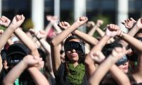 Con los ojos vendados y vestidas de negro, varias mujeres reunidas frente a la Corte Suprema de Justicia cantan comparsas en conmemoraci—n de la tragedia en el Hogar Seguro.