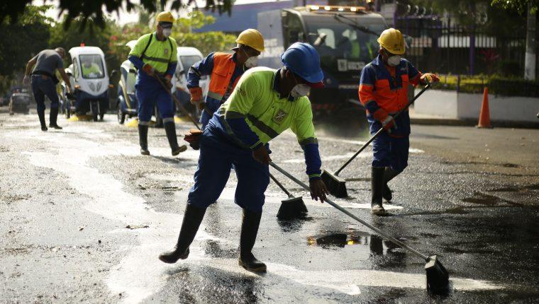 Trabajadores de la alcaldía de San Salvador realizan limpieza y desinfección de las principales calles. (Foto Prensa Libre: EFE)