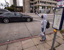 María vende máscaras faciales en la esquina de una calle después de perder su trabajo en medio de la pandemia de coronavirus en Los Ángeles, California, EE. UU. (Foto Prensa Libre: EFE).