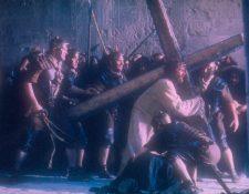 El actor Jim Caviezel que interpreta el papel de Jesús, carga la Cruz, en una escena de la película La Pasión de Cristo, dirigida por el también actor Mel Gibson. (Foto Prensa Libre: EFE)