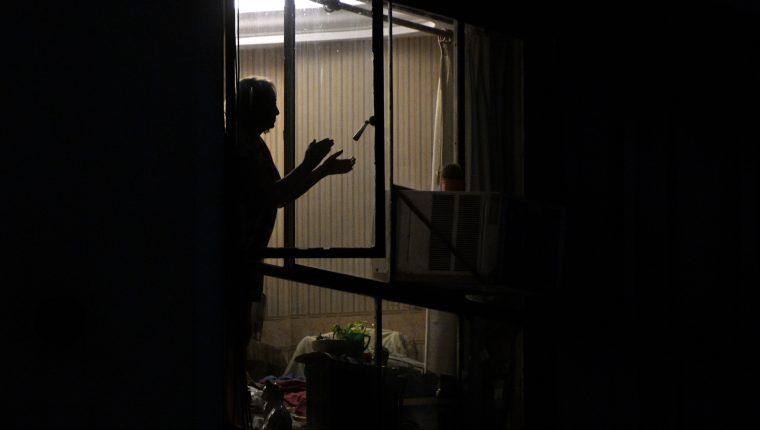 Dentro de sus apartamentos, cientos de argentinos aplauden para expresar su gratitud a los trabajadores de la salud todas las noches a las 9 p.m. (Foto Prensa Libre: AFP)