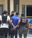 Autoridades trasladan a uno de los capturados señalados del asalto a un banco en Poptún, Petén. (Foto Prensa Libre: PNC).