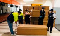 Trabajadores ordenan un cargamento de ataúdes de cartón, en Guayaquil, Ecuador. (Foto Prensa Libre: EFE)