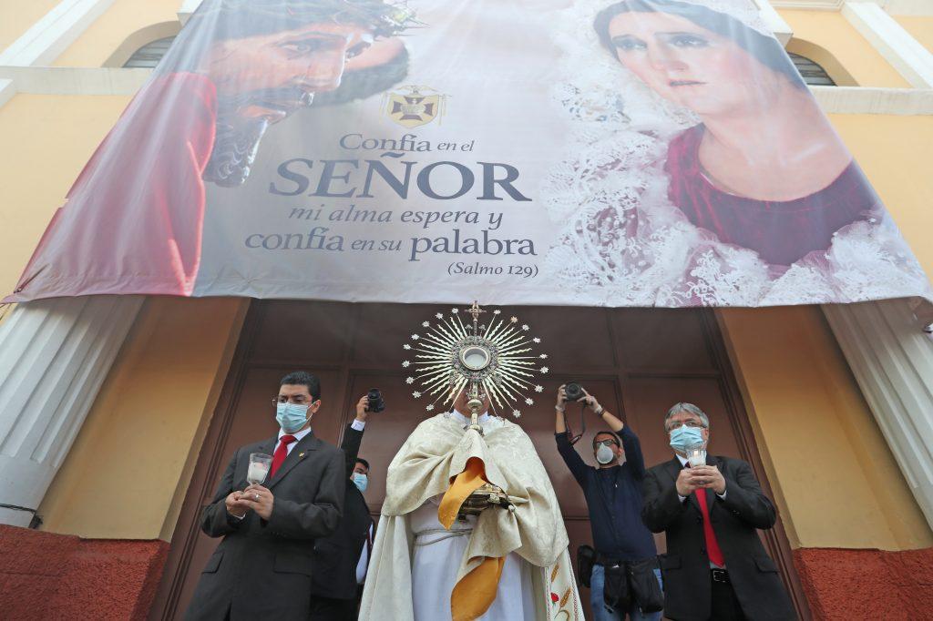 Representantes de la Junta Directiva de la Asociación de Jesús Nazareno de los Milagros acompañaron la procesión del Santísimo que salió al frente de la iglesia por unos minutos. Foto Prensa Libre: Óscar Rivas