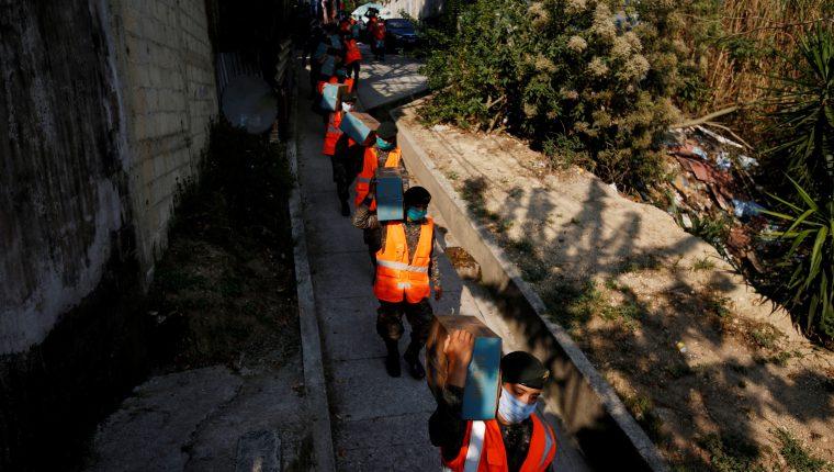Soldados del Ejército de Guatemala y policías reparten cajas con comida básica en el asentamiento Santa Rosita, este lunes, en la capital. (Foto Prensa Libre: EFE)