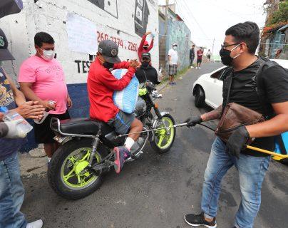 Vecinos de la colonia el incienso zona 3 desinfectan a las personas y veh'culos que ingresan a la colonia para evitar el contagio del Coronavirus. (Foto Prensa Libre: Erick Avila)