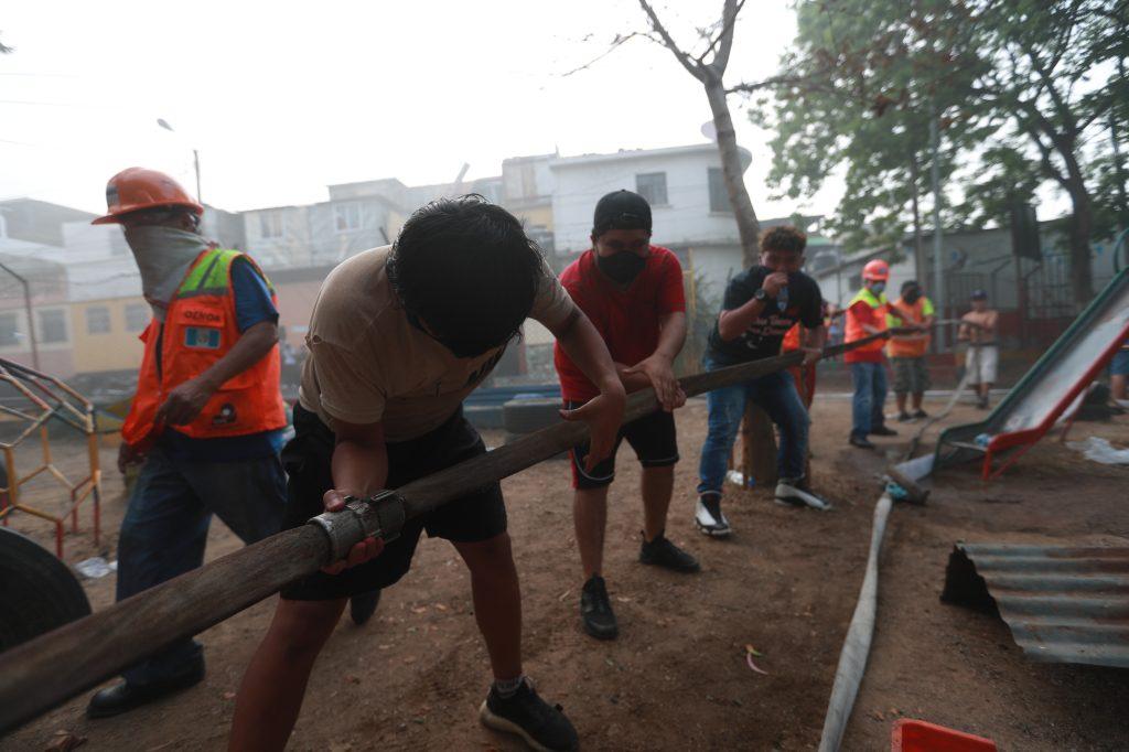 Para sacar las mangueras los vecinos apoyaron de nuevo a los socorristas. Foto Prensa Libre: Óscar Rivas