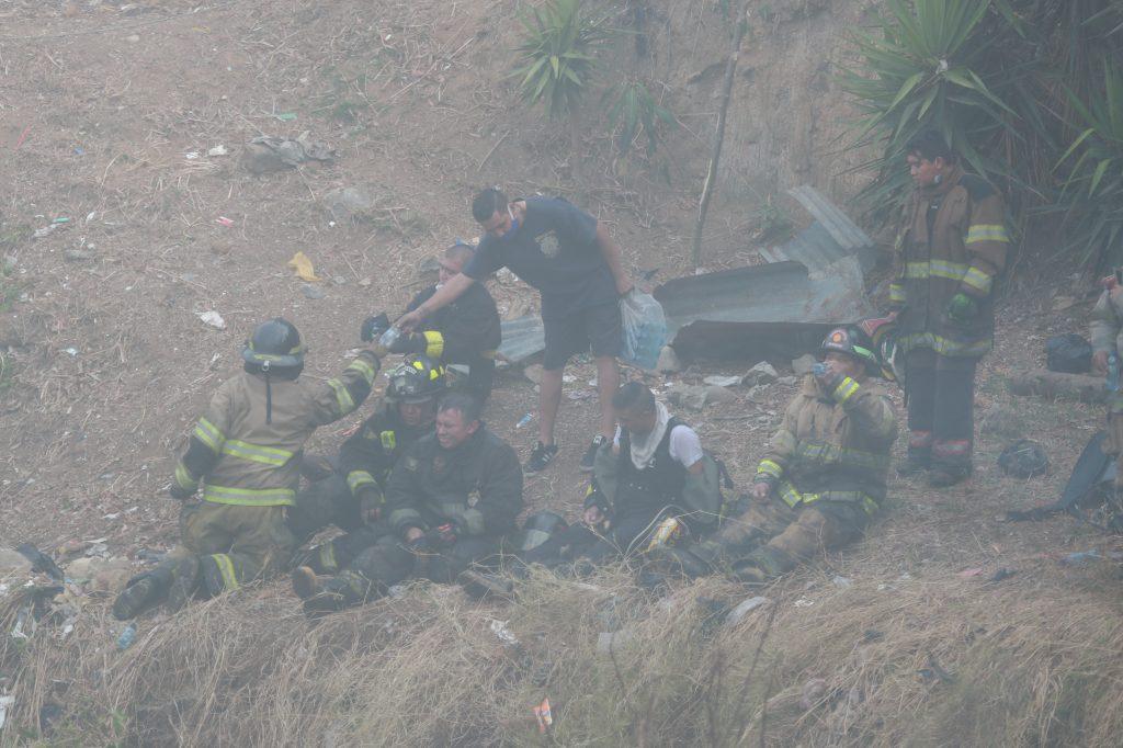 Un grupo de bomberos es atendido por un vecino que bajó a repartir agua pura después de su labor. Foto Prensa Libre: Óscar Rivas