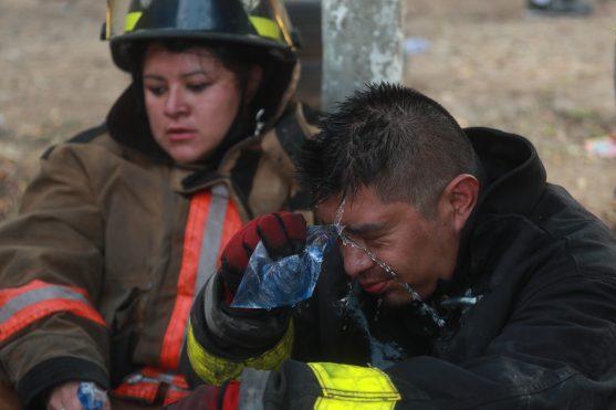 Los bomberos rociaron agua en sus rostros para limpiarlos después de haber subido hasta las colonias. Foto Prensa Libre: Óscar Rivas