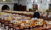 El padre Emilio Alvarado permanece entre las bancas de la concatedral de Chimaltenango, donde estas lucen las fotografías de los feligreses. (Foto Prensa Libre: Cortesía).