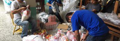 Personas altruistas preparan las bolsas con alimento que serán entregará a familias necesitadas en Quiché. (Foto Prensa Libre: Héctor Cordero)