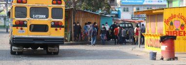 A la terminal de buses de Quiché llegaron dos autobuses con migrantes quienes luego de la evaluación médica fueron llevado su comunidad.  (Foto Prensa Libre: Héctor Cordero)