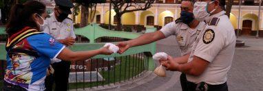 Una scout entrega panes a agentes de la Policía Nacional Civil en Huehuetenango durante una jornada de solidaridad con las fuerzas de seguridad. (Foto Prensa Libre. Mike Castillo)