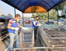 Trabajadores de la Municipalidad de Villa Nueva desinfectan carretas de compras en un mercado de la localidad. (Foto: @MuniVillaNueva)