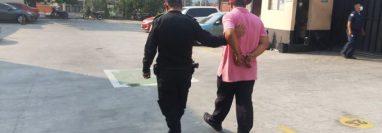 Carlos Humberto Cerna Martínez es conducido a un Juzgado por un agente de la Policía Nacional Civil. (Foto Prensa Libre: Cortesía)