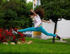 Una niña protegida con mascarilla salta en una calle en Córdoba, este domingo. Fotografía Prensa Libre:  EFE