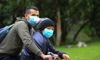 QUI01. QUITO (ECUADOR), 02/04/2020. Dos personas con mascarilla montan en bicicleta este jueves, por una calle de Quito (Ecuador). Los fallecidos en las últimas 24 horas por coronavirus en Ecuador se incrementaron hasta 120, 22 más que ayer miércoles, según las últimas cifras oficiales reveladas este jueves. EFE/ José Jácome
