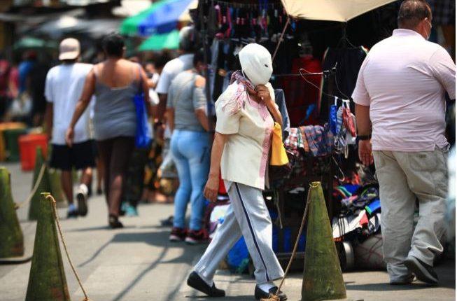 Una mujer camina con el rosto cubierto con una máscara para protegerse del coronavirus. (Foto Prensa Libre: Carlos Hernández)