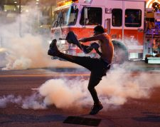 ATLANTA, GA - MAY 29: A man tosses back a tear gas canister during a protest on May 29, 2020 in Atlanta, Georgia. Demonstrations are being held across the US after George Floyd died in police custody on May 25th in Minneapolis, Minnesota.   Elijah Nouvelage/Getty Images/AFP == FOR NEWSPAPERS, INTERNET, TELCOS & TELEVISION USE ONLY ==