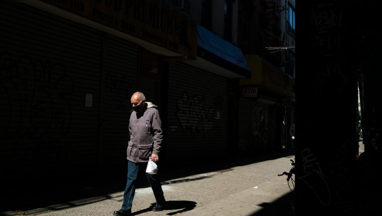 Un hombre camina por una calle con muchos negocios cerrados en Brooklyn, Nueva York. (Foto Prensa Libre: EFE)