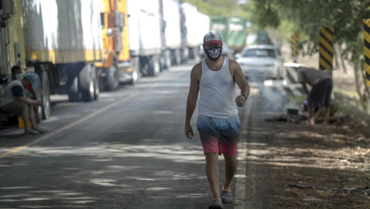 Un transportista de carga pesada, que se encuentra varado en Peñas Blancas en la frontera entre Nicaragua y Costa Rica, camina cerca a la ciudad de Rivas (Nicaragua). (Foto Prensa Libre: EFE)