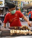 Un vendedor ambulante de comida atiende clientes en una calle de Taiwán, país que desde el inicio de la pandemia ha seguido con la normalidad. (Foto Prensa Libre: EFE)