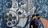 Personas usan tapabocas mientras pasan frente a un graffiti en la zona industrial, este miércoles en Bogotá, Colombia. (Foto Prensa Libre: EFE)
