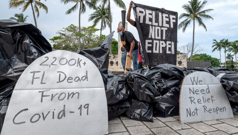 """Una persona despliega una pancartas frente a unas bolsas con supuestos """"cadáveres"""" que representan a los muertos por coronavirus este 27 de mayo durante la protesta contra la reapertura de la economía en el parque de la Antorcha de la Amistad en el centro de Miami, Florida. (Foto Prensa Libre: EFE)."""