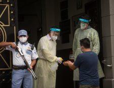 Personal médico reparte gel desinfectante a pacientes que entran a consulta en el Hospital General San Juan de Dios. (Foto Prensa Libre: EFE)