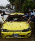 Residentes intentan empujar un taxi este domingo en una inundada calle de San Salvador (El Salvador). por las intensas lluvias generadas por la tormenta Amanda a su paso por la región. (Foto Prensa Libre: EFE)