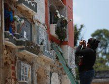 Uno de los colaboradores toma la foto de una tumba para mostrarla a uno de los deudos, que espera afuera del cementerio. (Foto Prensa Libre: Esbin García)
