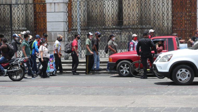 Personas hacen fila para recibir comida en la Plaza de la Constitución este 12 de mayo de 2020. (Foto Prensa Libre: Érick Ávila).