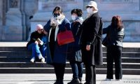 People wearing protective masks walk in the Piazza del Duomo in the northern city of Milan on February 28, 2020. - Italy urged tourists spooked by the novel coronavirus COVID-19 not to stay away, but efforts to reassure the world it was managing the outbreak were overshadowed by confusion over case numbers. (Photo by Miguel MEDINA / AFP)