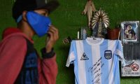 A kid walks pass a replica of Argentina's football team jersey used during the final of the FIFA World Cup Mexico '86, handwrited and signed by former football star Diego Maradona hangs from a catholic altar in a community kitchen during the lockdown imposed by the government against the spread of the new coronavirus, COVID-19, in Jose C. Paz, Buenos Aires, Argentina, on May 8, 2020. - Maradona's signed jersey will be raffled among those who donate food to feed people at a working class neighborhood called Rene Favaloro. (Photo by JUAN MABROMATA / AFP)