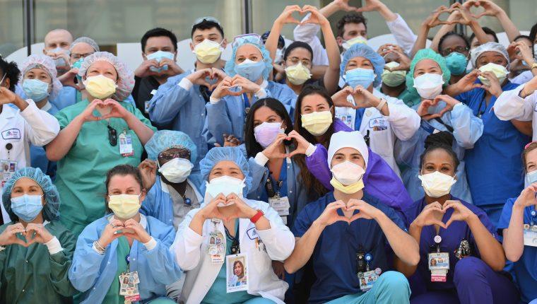 Enfermeros y encargados de la salud realizan con sus manos un gesto de corazón en celebración por el Día Internacional de la enfermera en las afueras del hospital Mt. Sinai Queen, en Nueva York. Fotografía Prensa Libre: Angela Weiss / AFP.