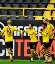 El defensa portugués Raphael Guerreiro celebra con sus compañeros uno de sus dos goles con el Dortmund. (Foto Prensa Libre: AFP)
