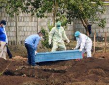 Trabajadores de Salud con trajes protectores entierran a una víctima de covid-19 en el cementerio de Managua. (Foto Prensa Libre: AFP)