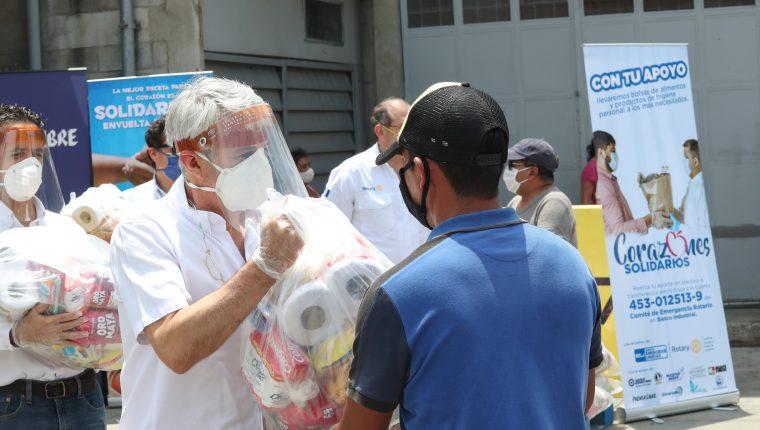 Adolfo Paiz, de Avícolas Unidas, entrega una bolsa de víveres a una persona de la economía informal. Foto Prensa Libre: Norvin Mendoza
