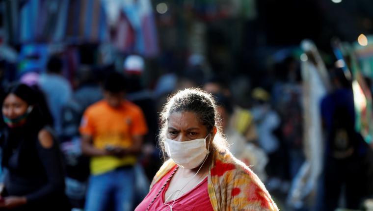 Una mujer en el mercado de La Terminal utiliza la mascarilla obligatoria como medida de prevención frente al covid-19. (Foto Prensa Libre: EFE)