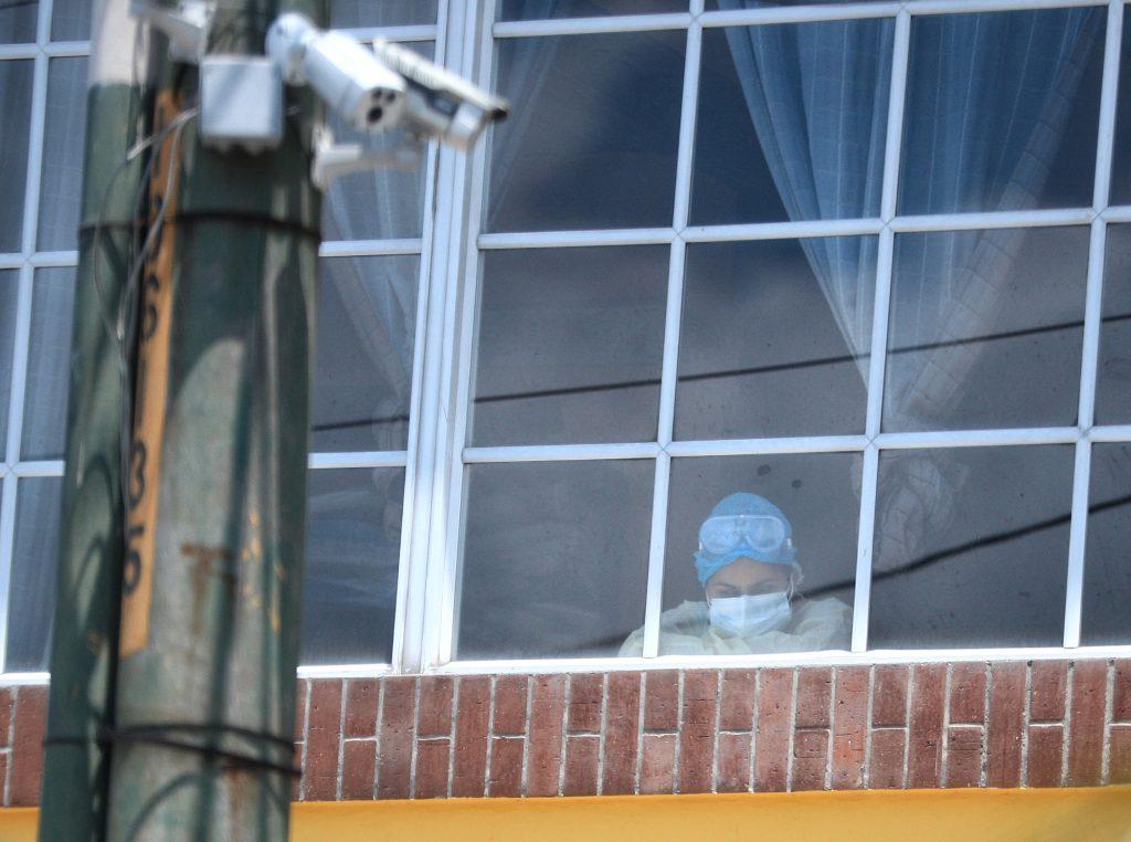 Una persona que labora en un hospital temporal del Instituto Guatemalteco de Seguridad Social toma un breve descanso y se acerca a una de las ventanas del lugar. Foto Prensa Libre: Carlos Hernández
