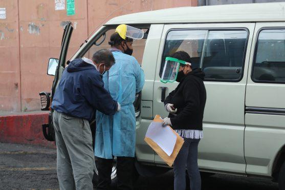 Trabajadores de una funeraria toman sus prevenciones antes de recibir el cuerpo de una persona fallecida en la morgue del hospital San Juan de Dios